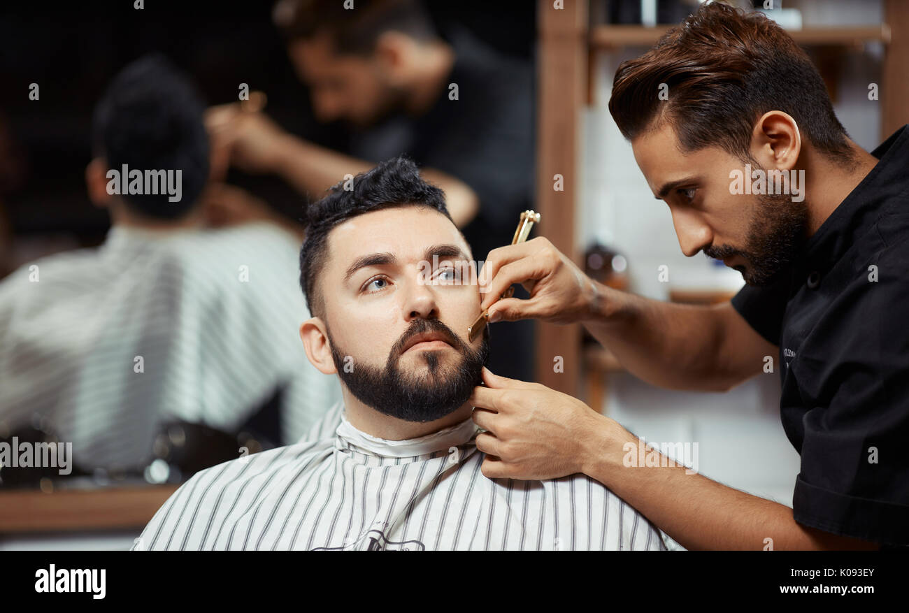Concentrated barber working with man - Stock Image