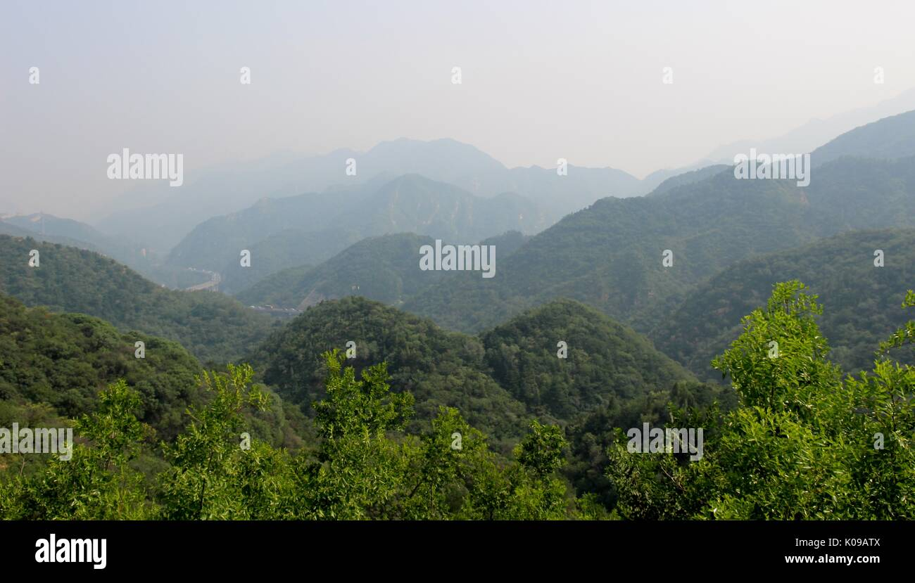 Mountains disappearing into the smog off the Great Wall of China - Stock Image