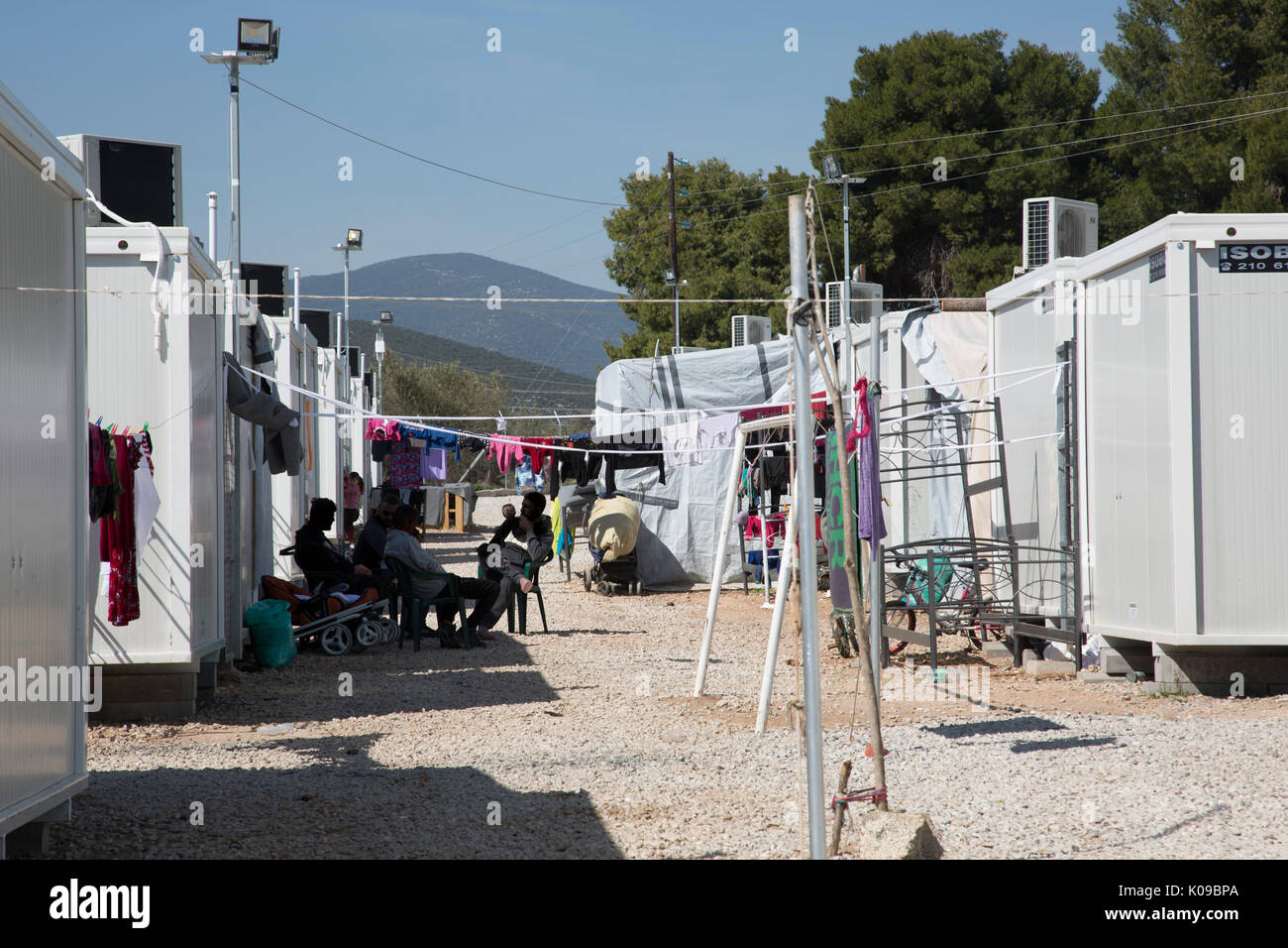 Men sitting in the shade between rows of prefabricated accommodation units at Ritsona Refugee Camp, Greece. - Stock Image