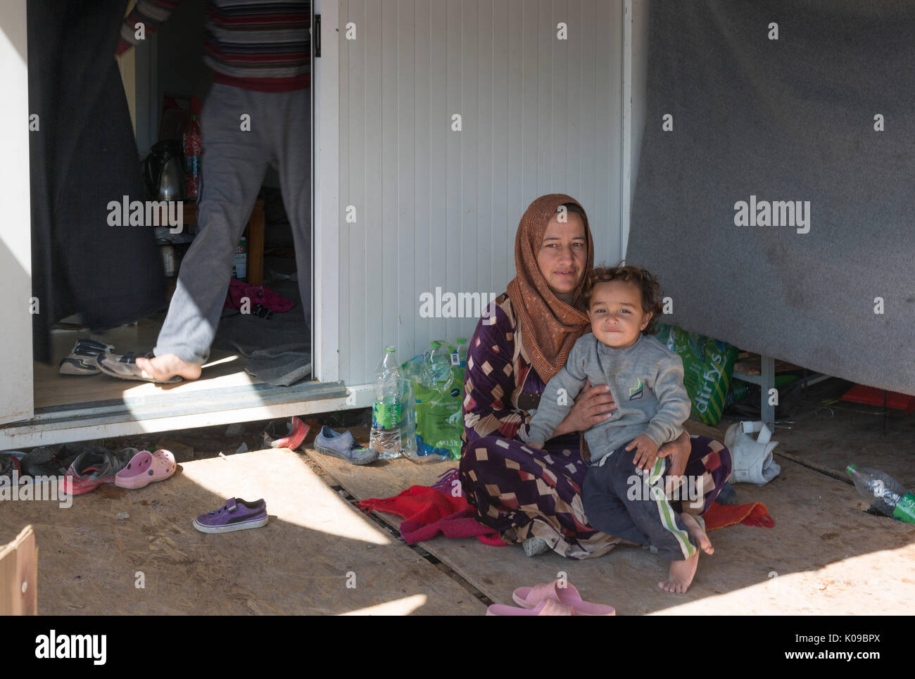 A refugee mother sits in the shade of her prefabricated home in the Ritsona refugee camp for Syrians in Greece. Her husband's legs in doorway behind. - Stock Image
