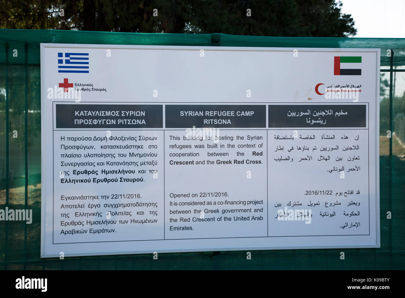 A sign at the entrance to Ritsona Refugee Camp in Greek, English and Arabic tells of cooperation of Greek Red Cross and Emirates Red Crescent. - Stock Image