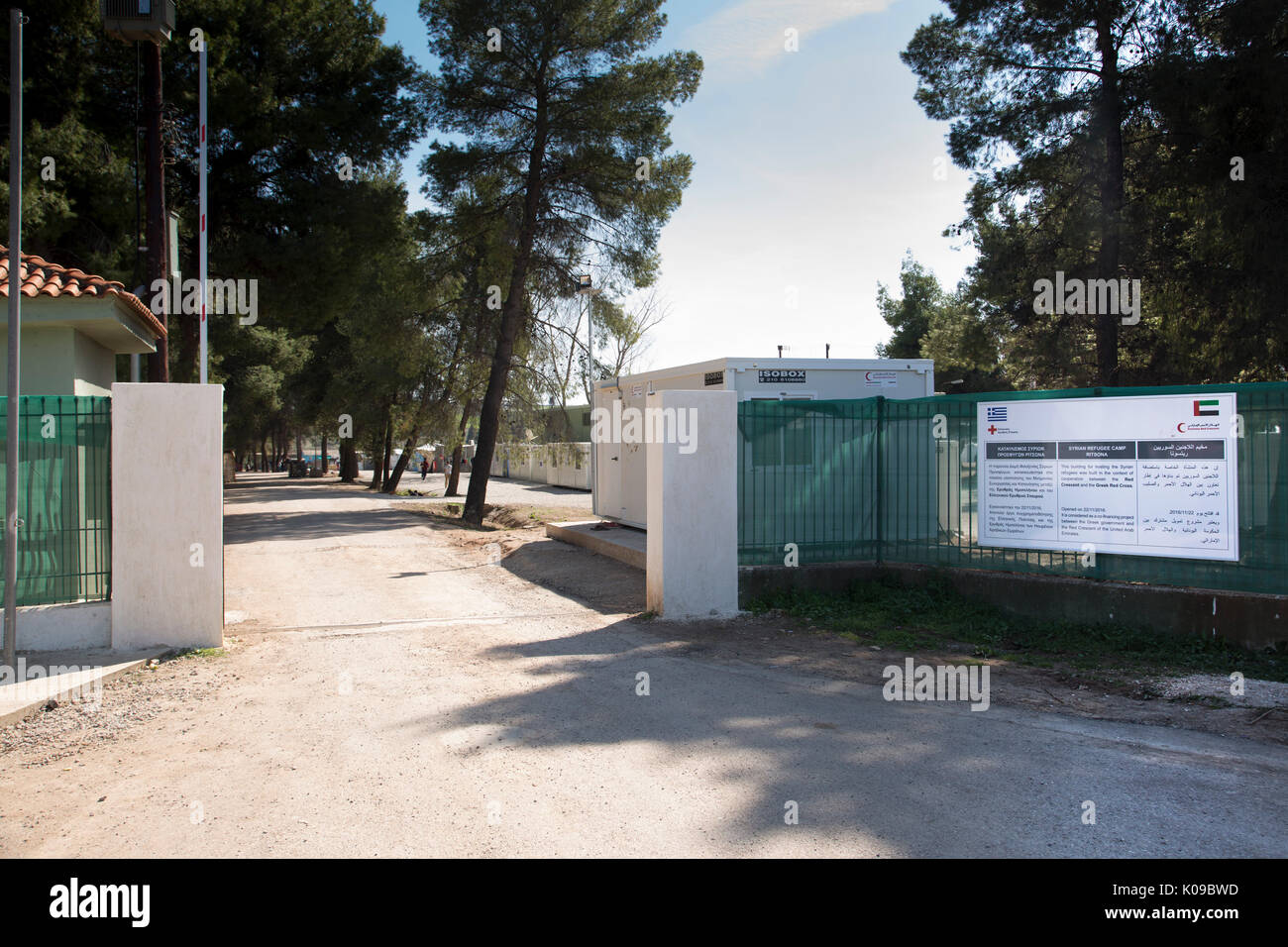 Entrance gate of Ritsona Refugee Camp with a sign in Greek, English and Arabic telling of cooperation of Greek Red Cross and Emirates Red Crescent. - Stock Image