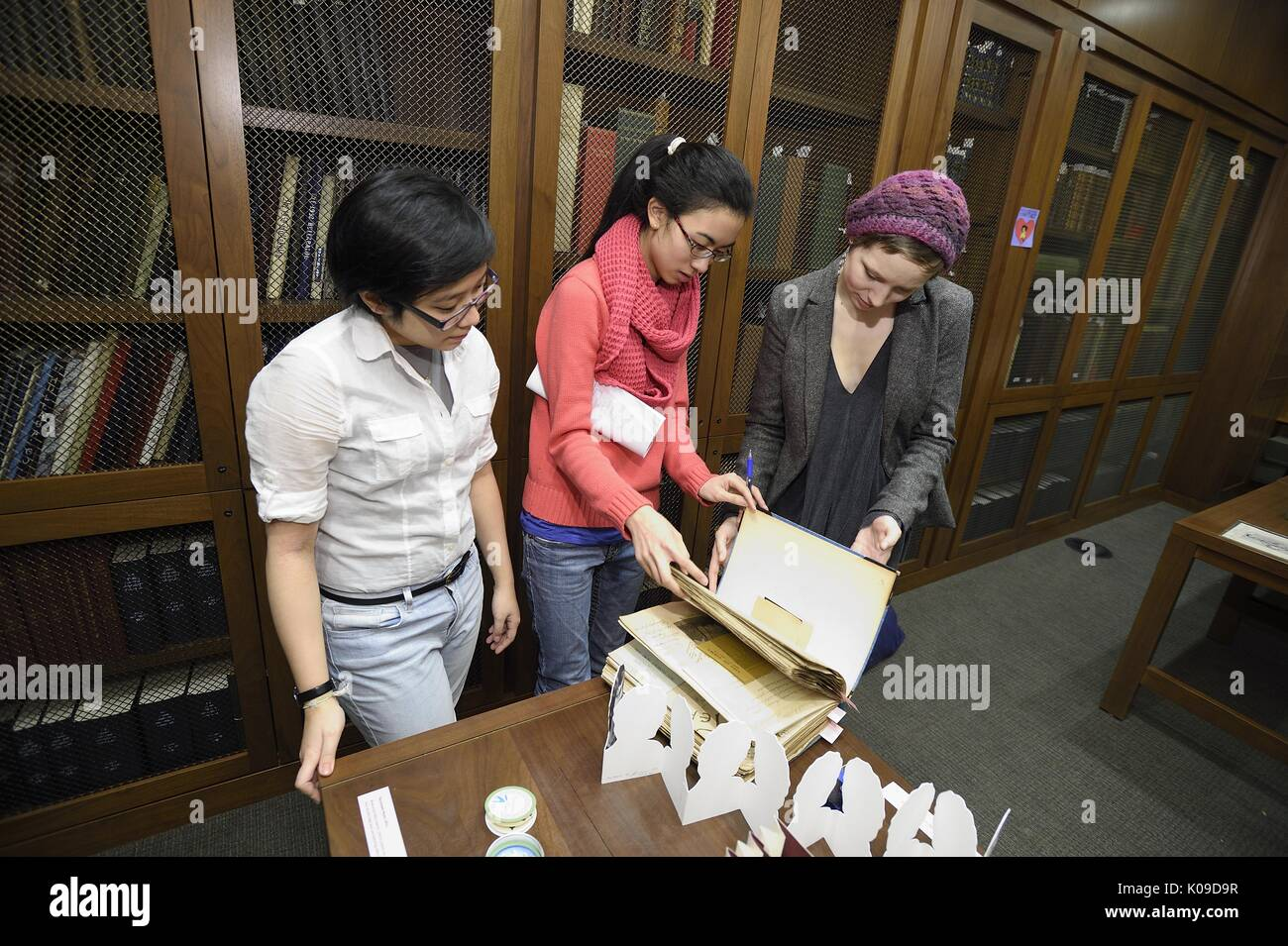 Three female college students are beginning to look through a binder at the library event called Dirty Books and Longing Looks, February 11, 2016. - Stock Image