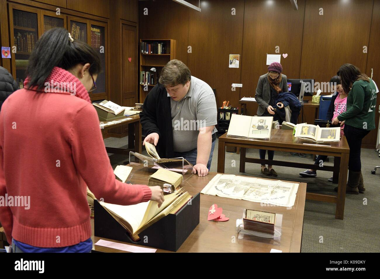 Students scattered around a room all looking down and interacting with different artifacts at the library event, Dirty Books and Longing Looks, February 11, 2016. - Stock Image