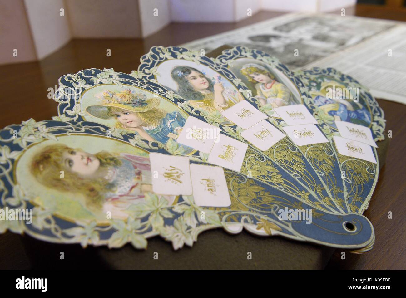 A paper fan artifact with faces of female children on it on display at the Dirty Books and Longing Looks event held at the library, February 11, 2016. - Stock Image