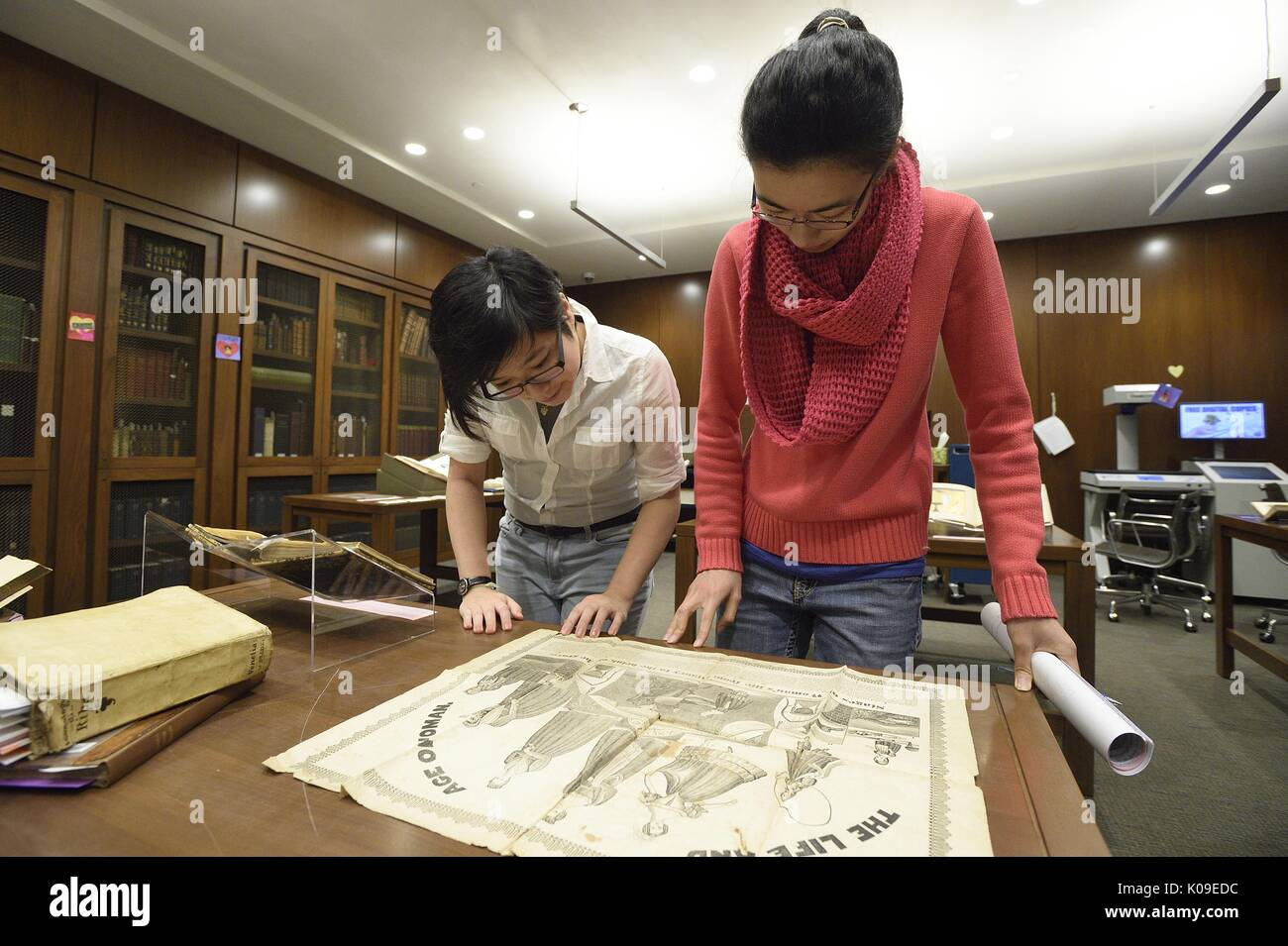 Two female college students are looking down at a large illustration artifact at the library event called Dirty Books and Longing Looks, February 11, 2016. - Stock Image