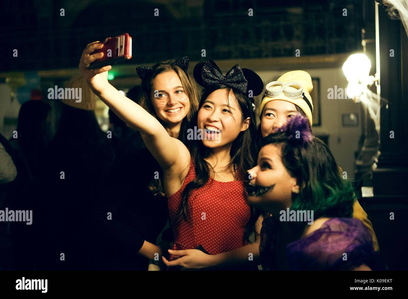 A group of four female college students dressed in costumes; one student as Minnie Mouse holding a phone taking a selfie another student dressed in the ...  sc 1 st  Alamy & A group of four female college students dressed in costumes; one ...