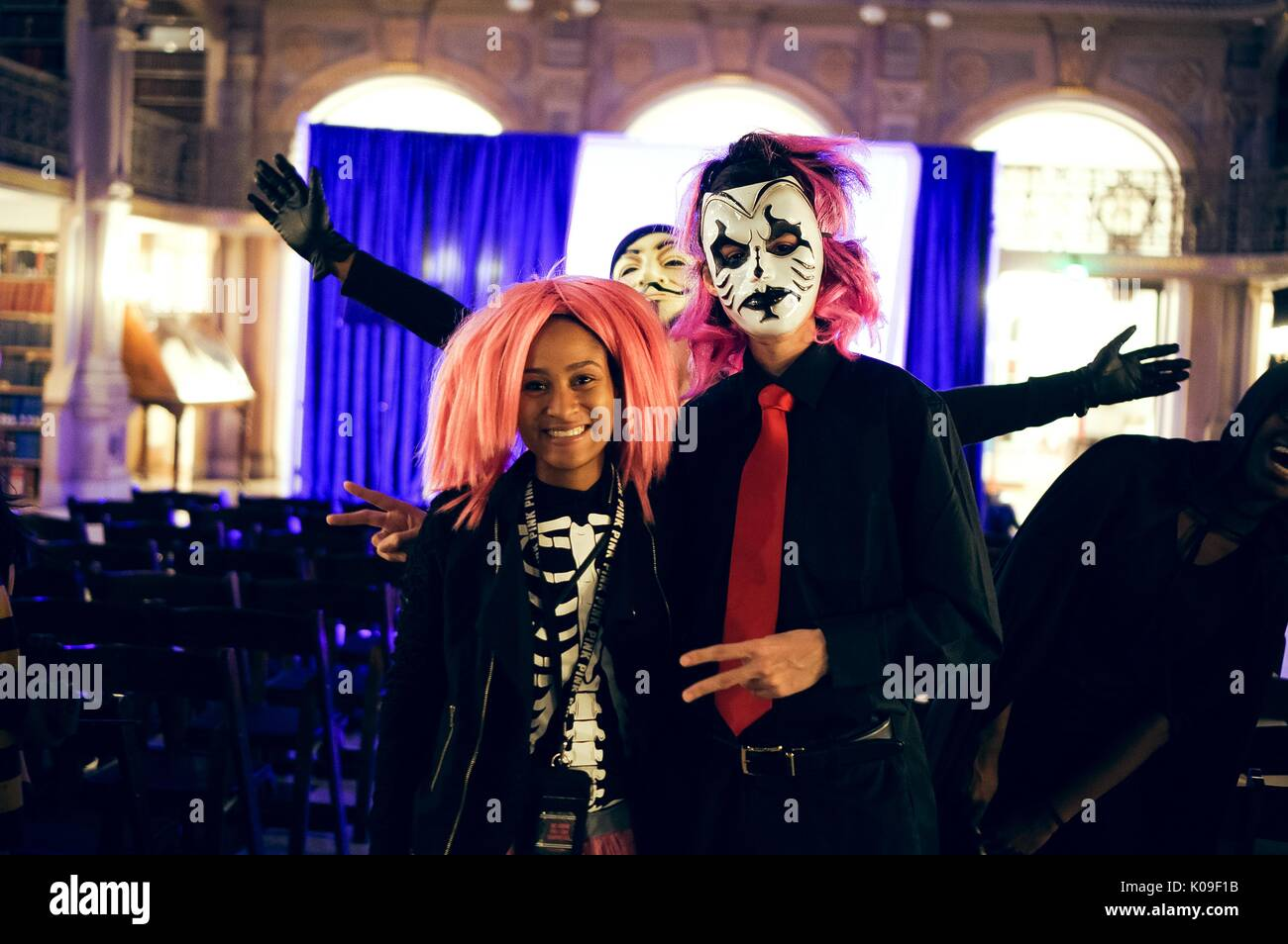 Two students, female on the right dressed in a pink wig and a black skeleton shirt, male on the right wearing a black shirt with a rd tie and black and white face paint with a bright pink wig, a student wearing the Anonymous mask photobombing behind them with arms outstretched; smiling facial expressions, Halloween at Peabody, October 31, 2015. Courtesy Eric Chen. - Stock Image