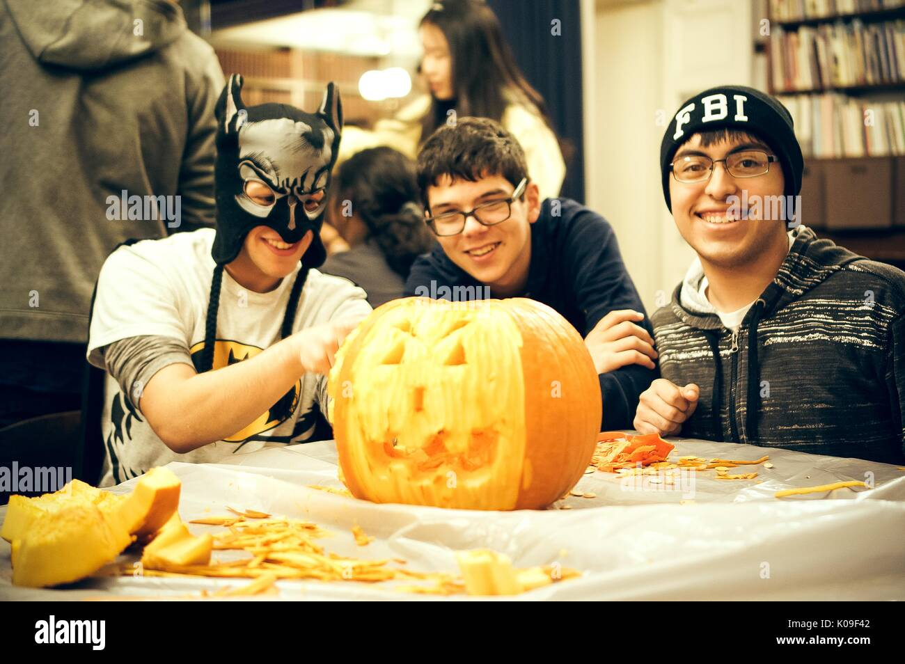 Three male students seated around a table carving a pumpkin, the leftmost student wearing a mask, the middle student without a conspicuous costume, the rightmost student wearing a beanie that reads 'FBI'; all with smiling facial expressions, Halloween at Peabody, October 31, 2015. Courtesy Eric Chen. - Stock Image