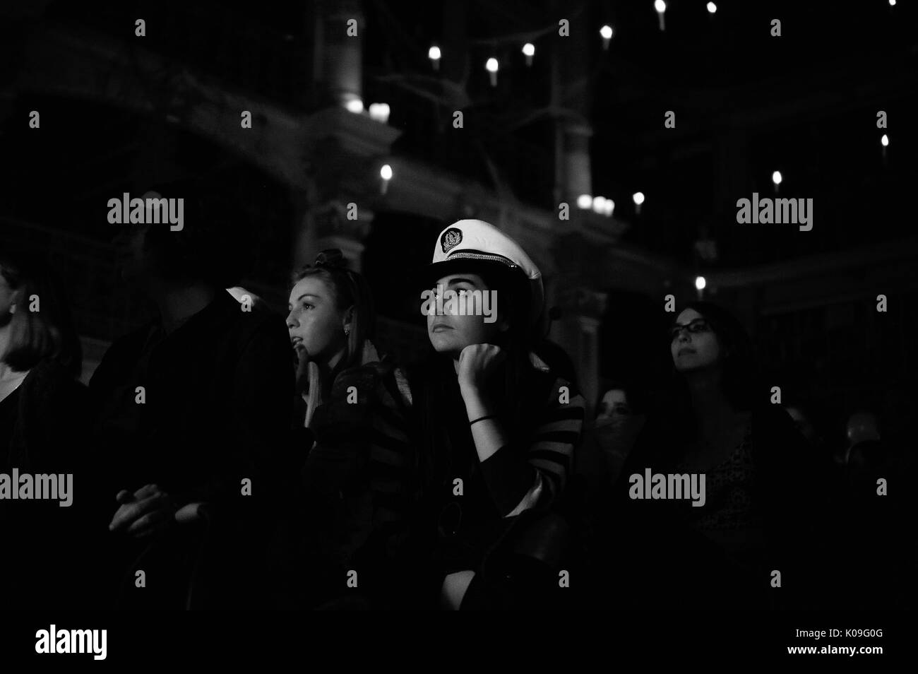 A female college student in a sailor hat looks toward the stage as she sits among other audience members as the library lights are off and the special lights hang and glow from up above, 2015. Courtesy Eric Chen. - Stock Image