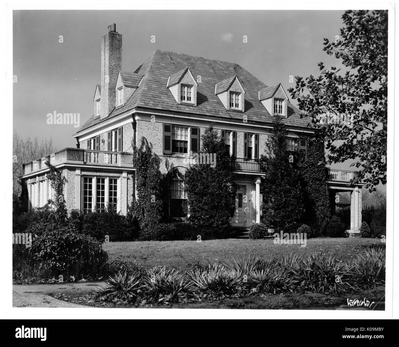 Landscape shot of a large three story house with a chimney, balconies on each side with well kept landscaping surrounding the house, Roland Park / Guilford, Baltimore, Maryland, 1910. This image is from a series documenting the construction and sale of homes in the Roland Park/Guilford neighborhood of Baltimore, a streetcar suburb and one of the first planned communities in the United States. The neighborhood was segregated, and is considered an early example of the enforcement of racial segregation through the use of restricted covenants. - Stock Image