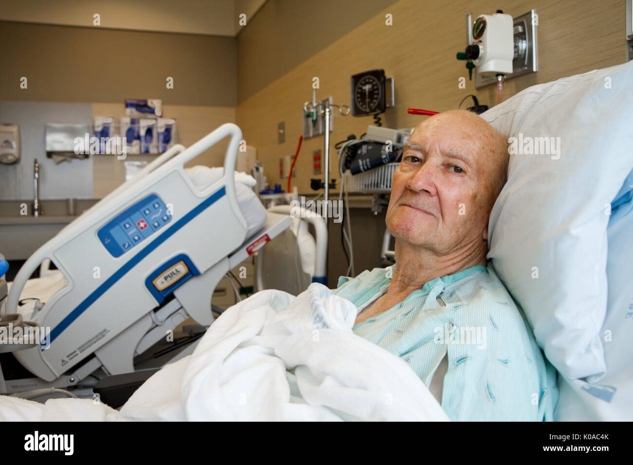 Elderly Male Patient Sitting Up in Hospital Bed - Stock Image