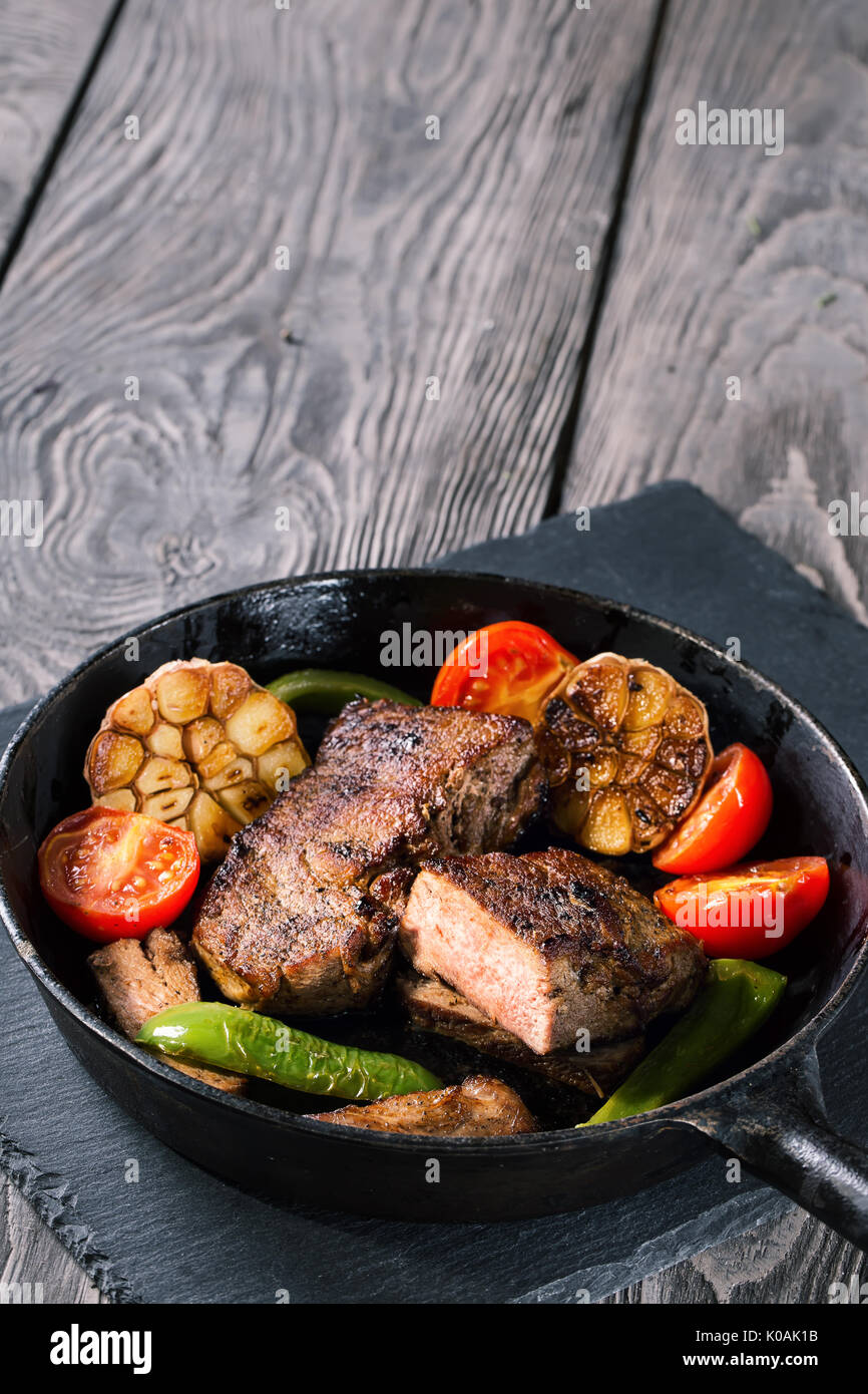 Slightly fried beef steak with vegetables on cast-iron frying pa Stock Photo