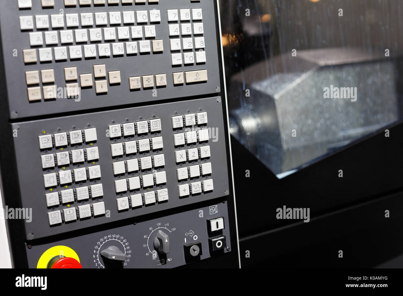 CNC machining center with control panel on the foreground. Selective focus. - Stock Image