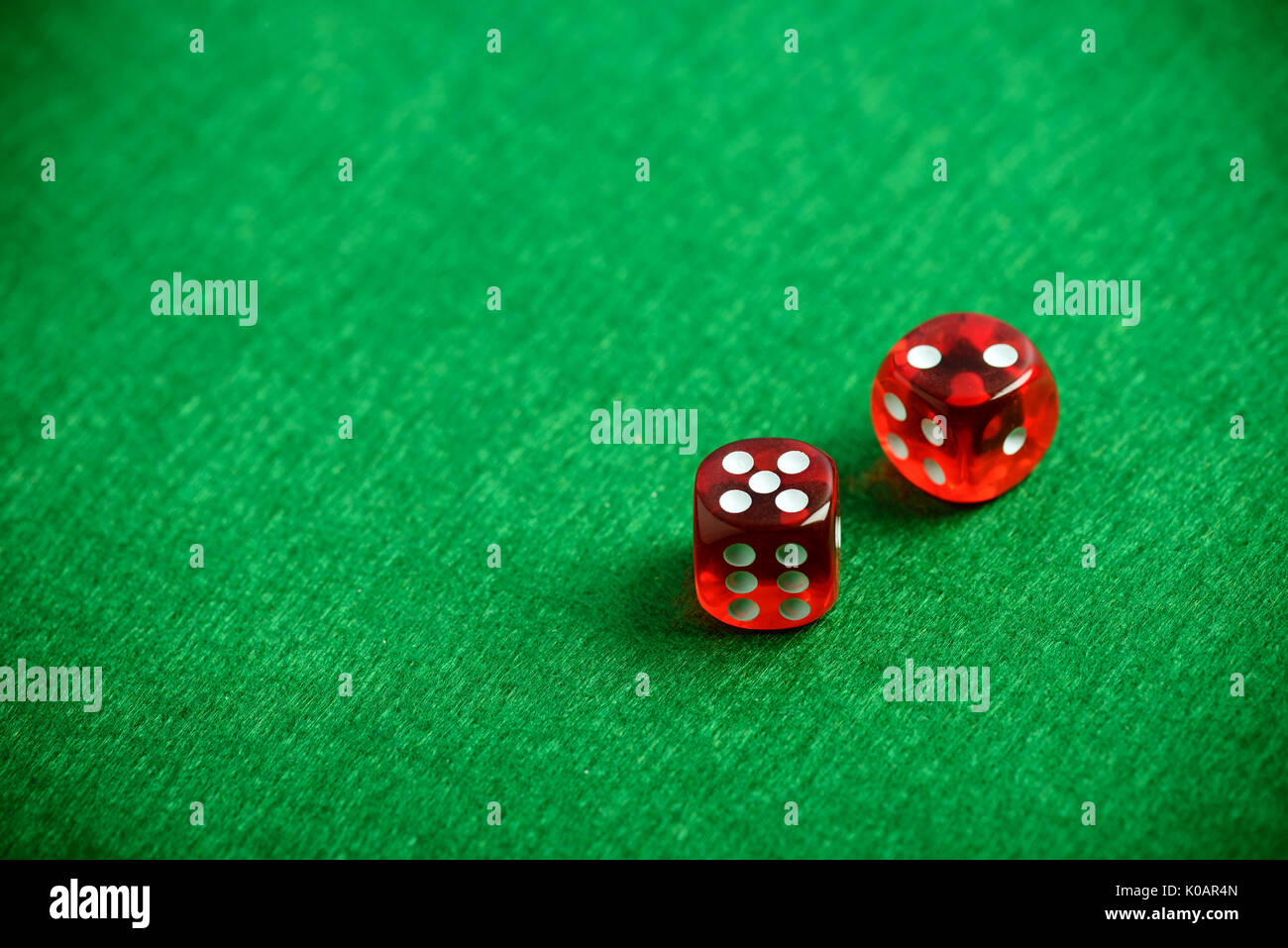 Red poker dices on casino table background - Stock Image