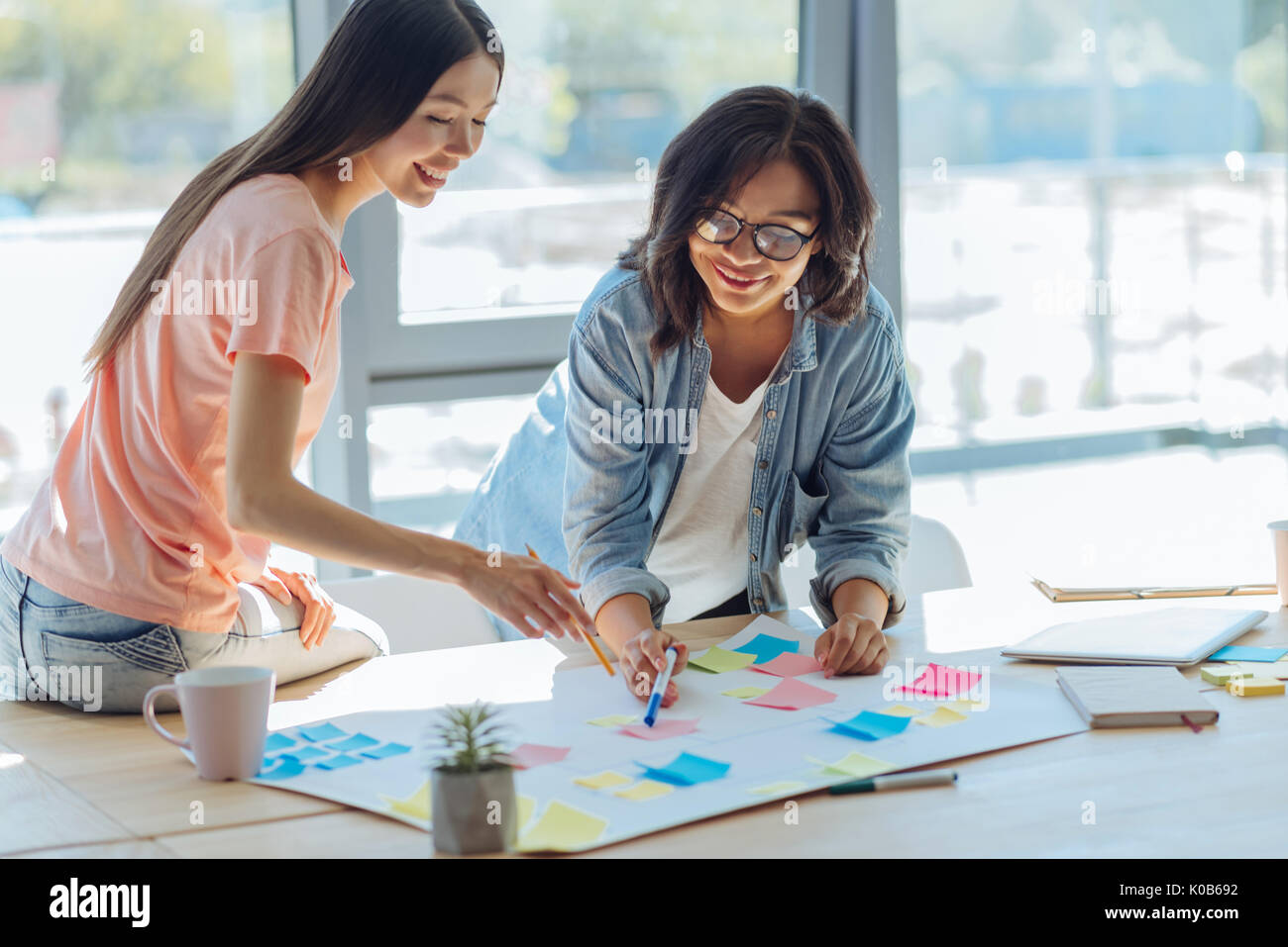 Pleasant smart friends doing a project - Stock Image
