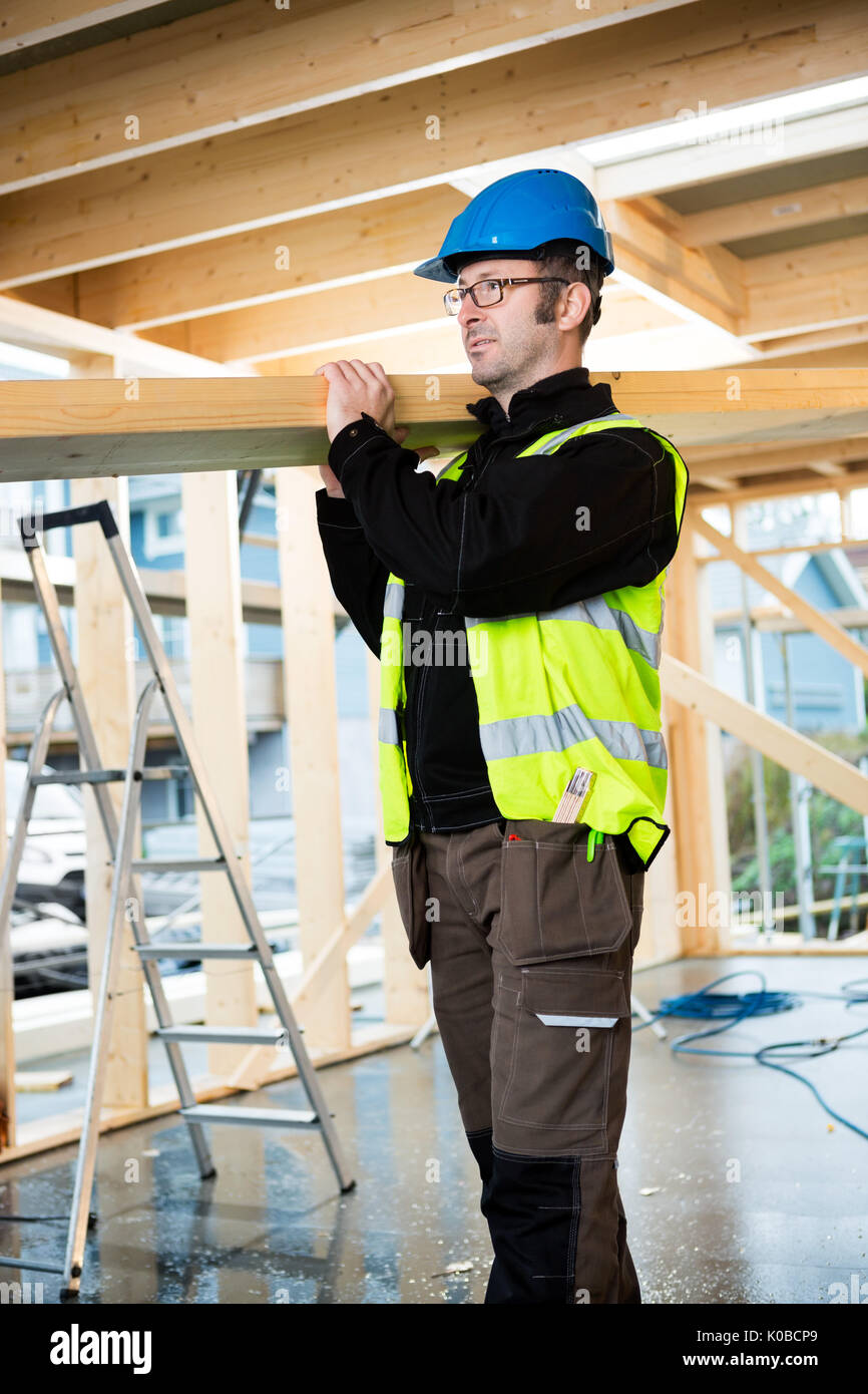 Confident Carpenter Carrying Wood On Shoulder At Site Stock Photo
