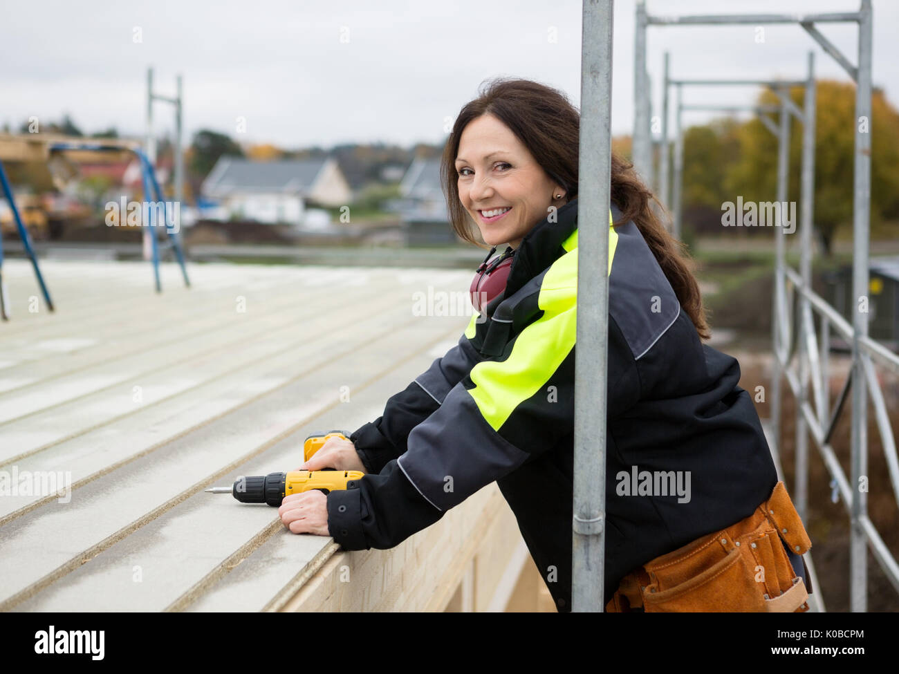 Female Carpenter Smiling While Holding Drill Machine At Roof - Stock Image