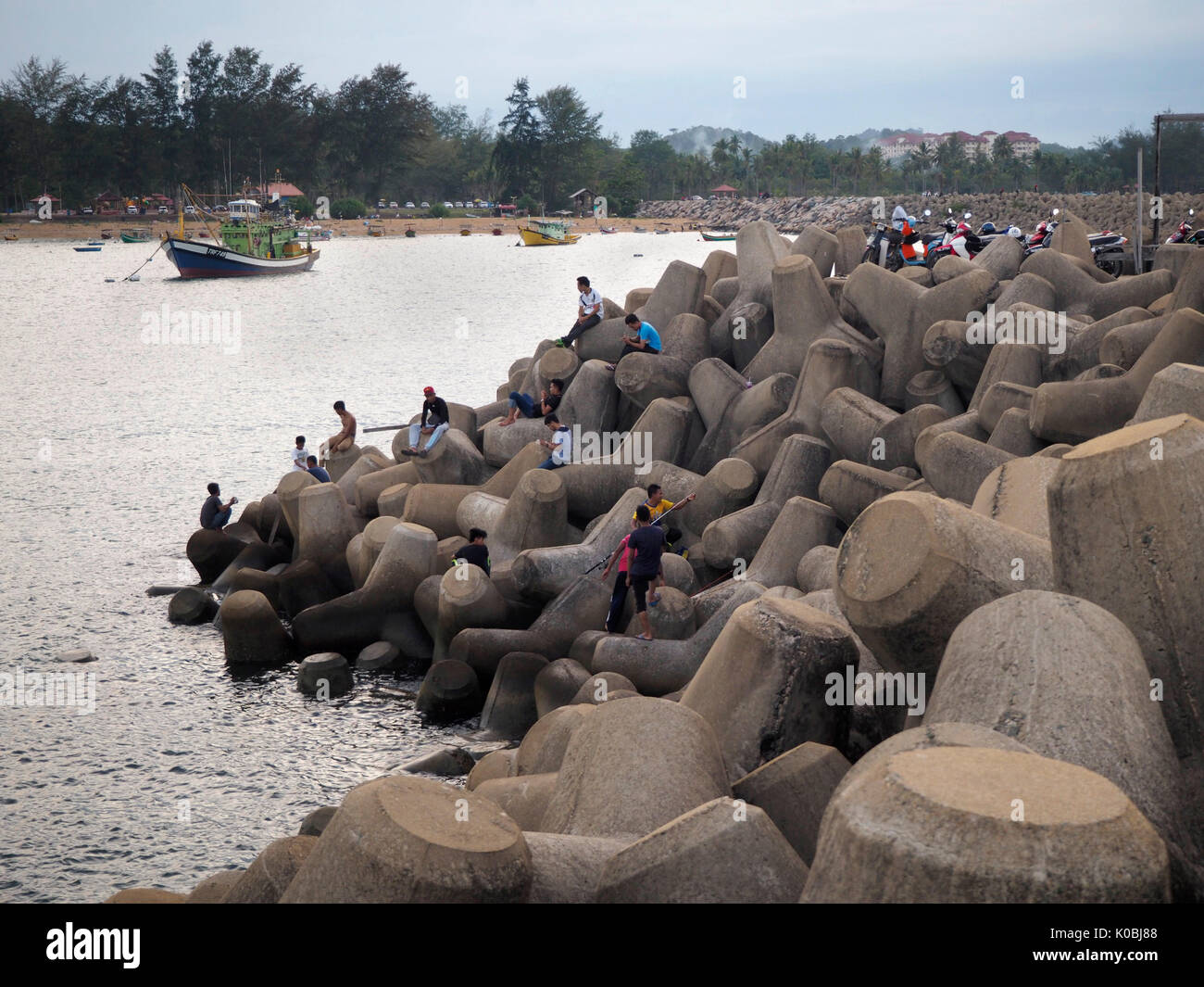 People on tetrapod wave breaker - Stock Image