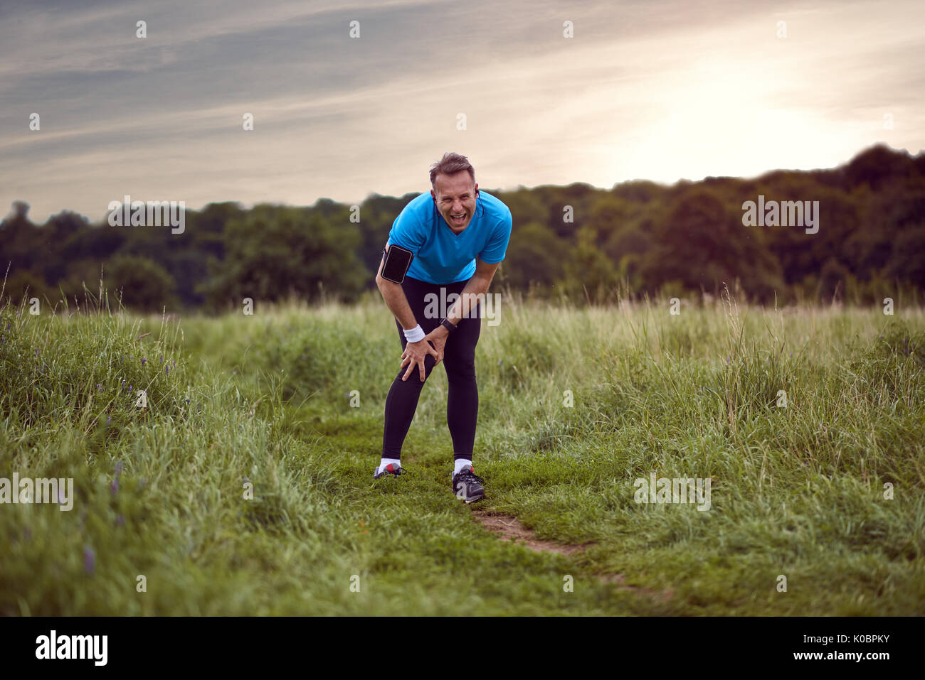 An exercising man in fit wear while running outdoors, stop to clutch an injured knee. - Stock Image