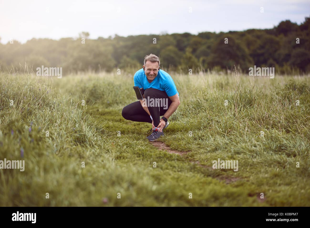 An exercising man in fit wear while running outdoors, stop to clutch an injured ankle. - Stock Image