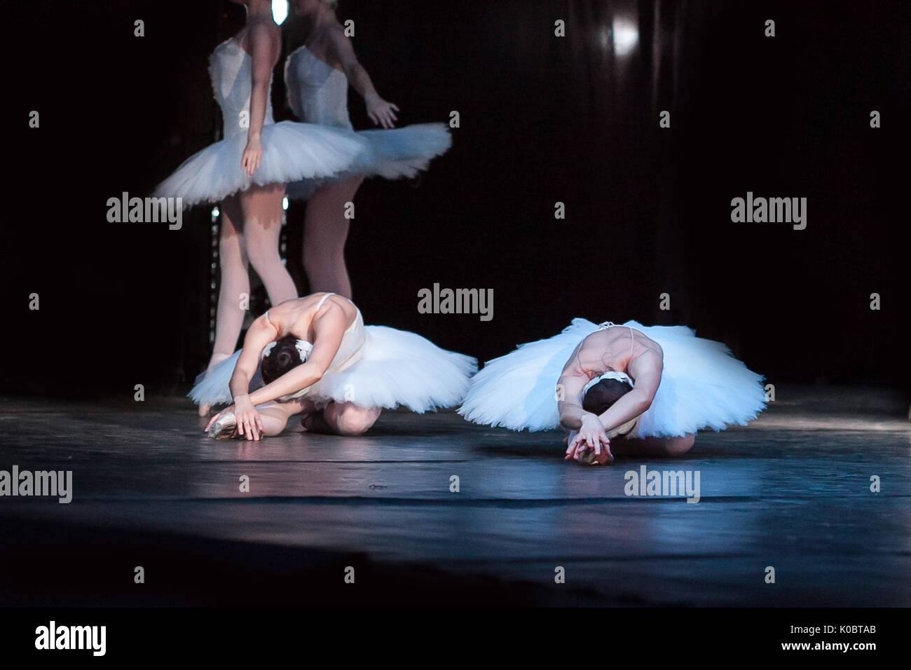 dancing, agility, beauty concept. thin and adorable female ballet dancers dressed in shiny white tutus and leotards, they are lying on the stage of the theater with their arms folded - Stock Image