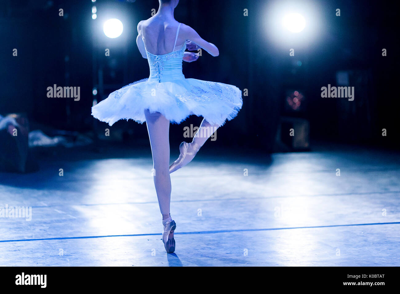glory, dream, choreography concept. slender silhouette of female ballet dancer in the stage lights wearing beautiful tutu turning around like statuette in music box - Stock Image