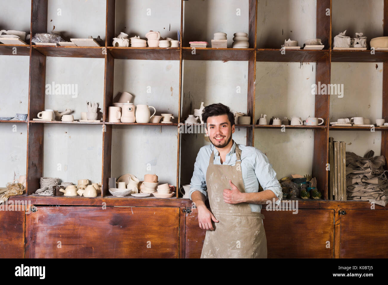 pottery, tools, ceramics art concept - happy handsome young male dressed in an apron stand with finished utensils, smiling ceramist at workplace with baked cups and jugs at background. - Stock Image