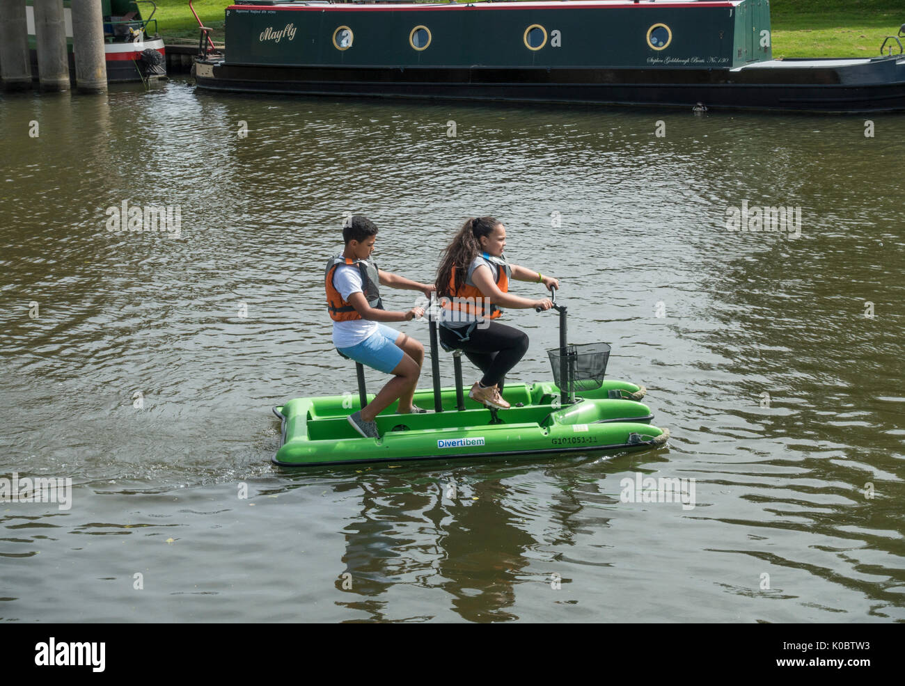 Youths pedalling a water bike on the river Great Ouse Stock Photo