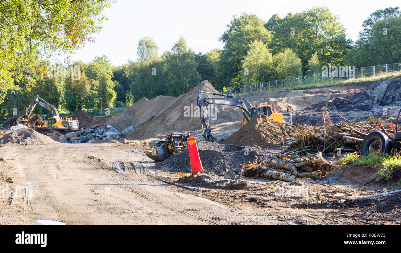 Heavy duty excavators at building site digging and moving topsoil ahead of construction  Model Release: No.  Property Release: No. - Stock Image