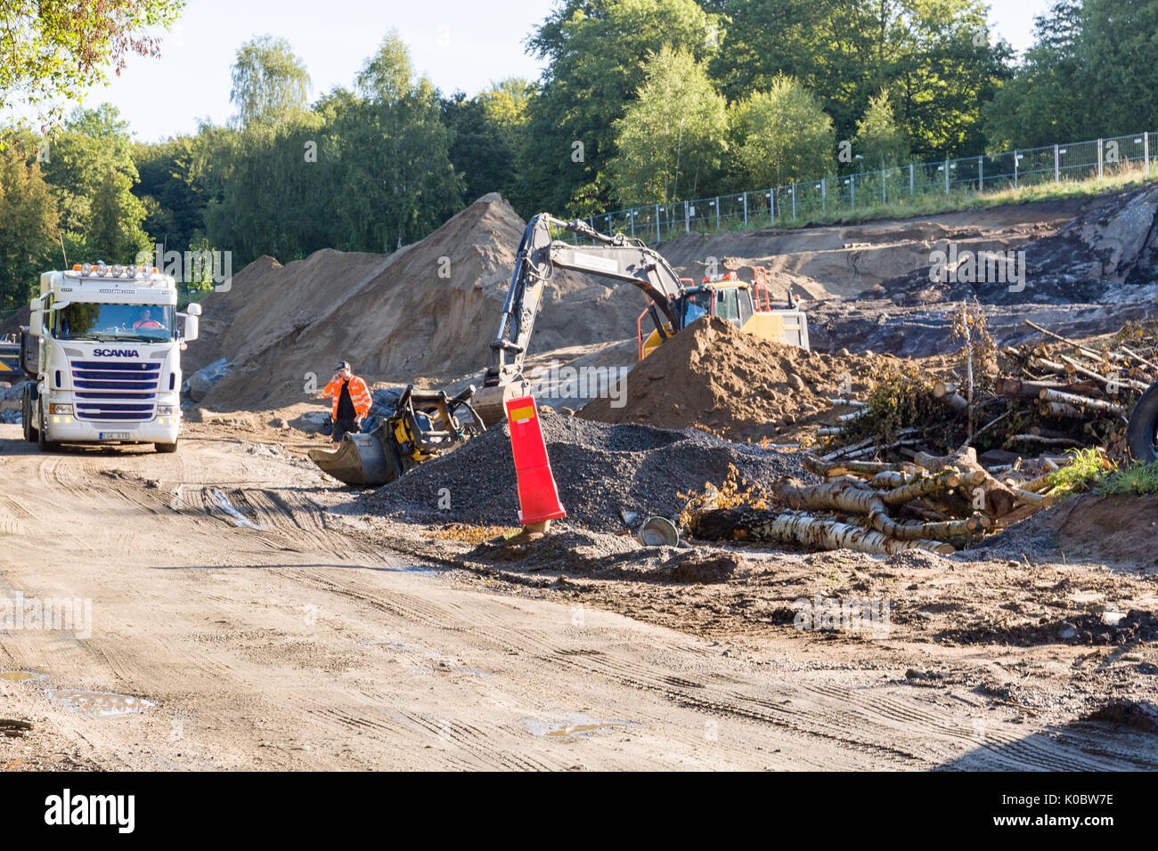 Heavy duty excavators at building site digging and loading trucks lorries with topsoil ahead of construction  Model Release: No.  Property Release: No. - Stock Image