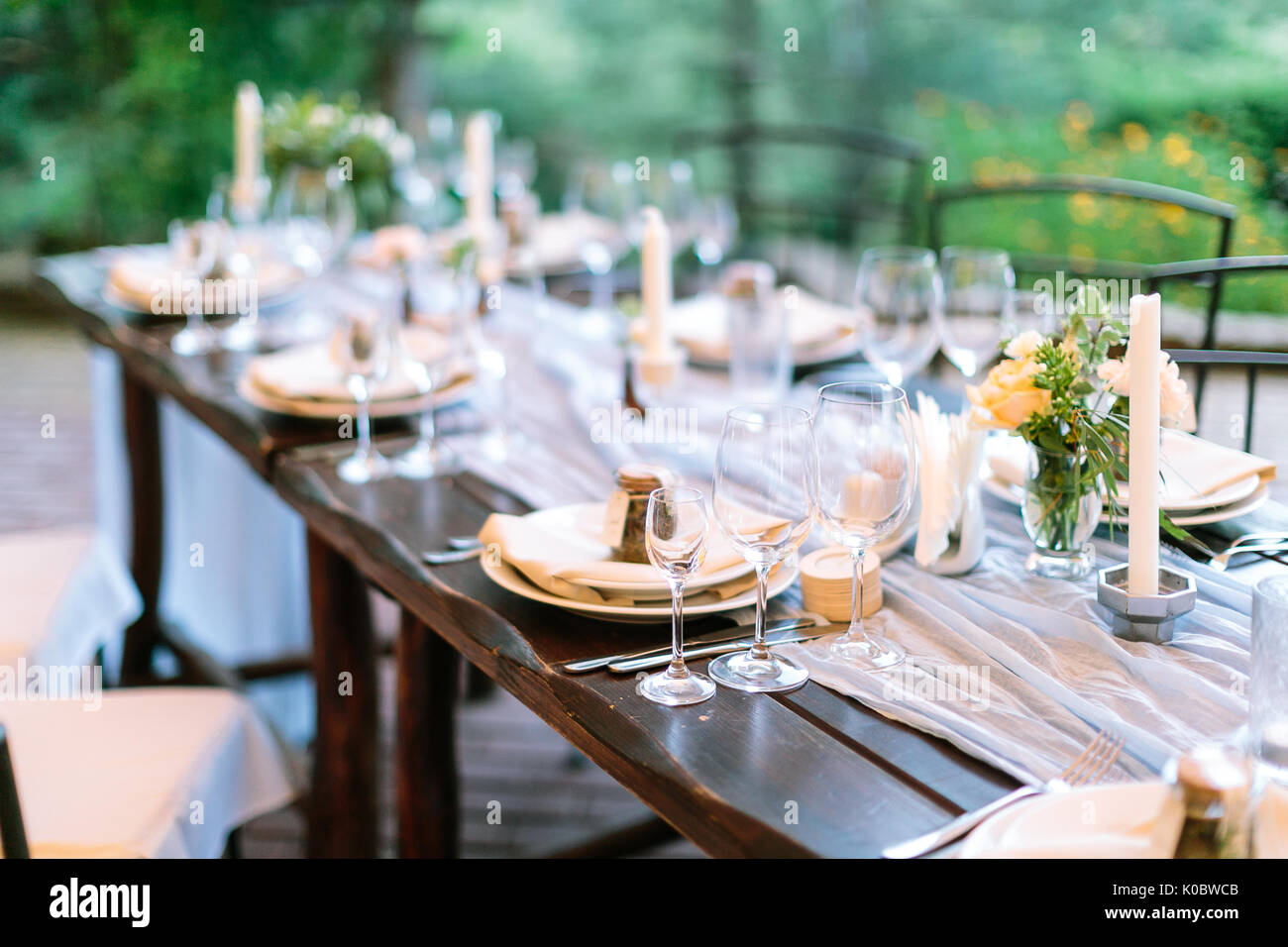 fest, dinner, tradition concept. long oaken table served for celebration with silverware, dishes and transparent dazzling glasses, flowers and candles in interesting holders in form of octagonal - Stock Image