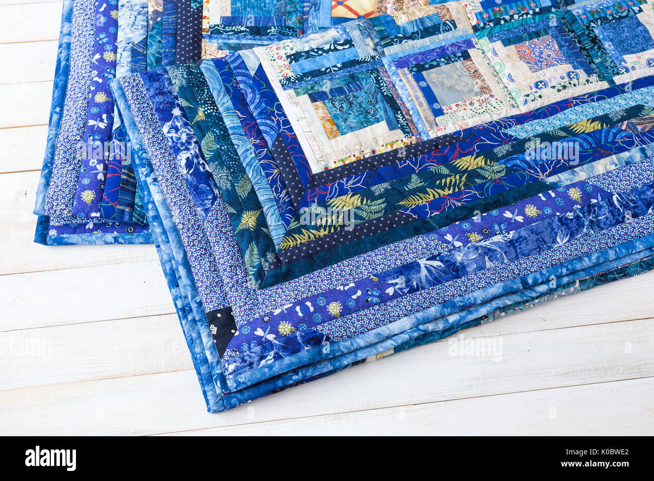 decoration, comfort, passion, fondness, stitching, patchwork concept - two dark blue quilt neatly maded of different patches with interesting floral pattern and almost invisible stitches - Stock Image