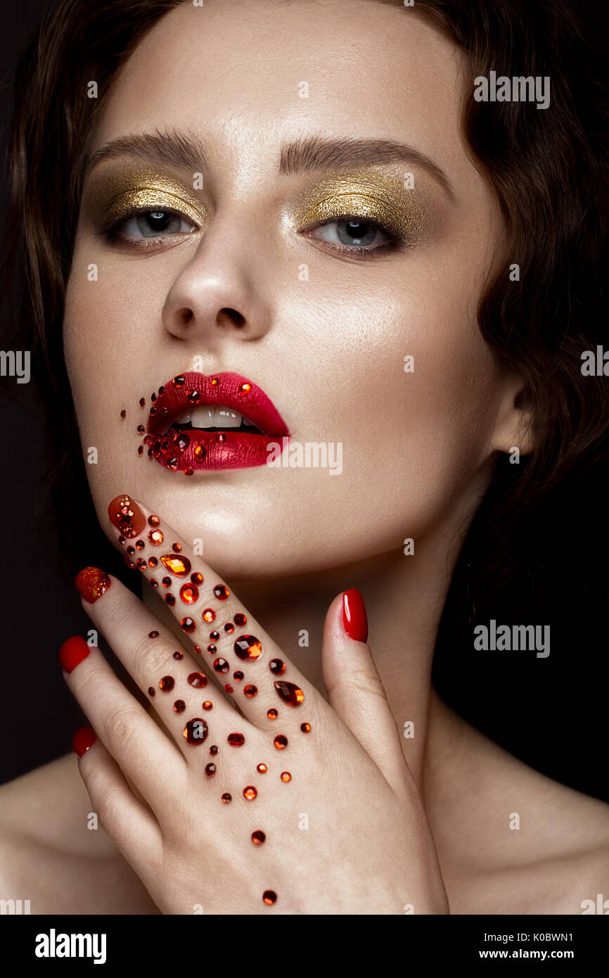 Beautiful girl with evening make-up, red lips in rhinestones and ...