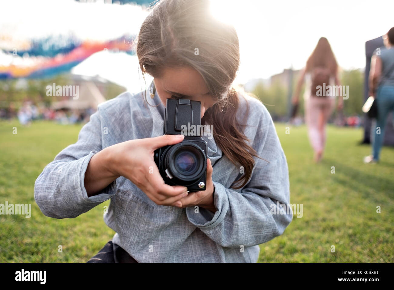 Pretty caucasian female using film photocamera. Traveling woman taking photo on vintage camera outdoor in summer - Stock Image