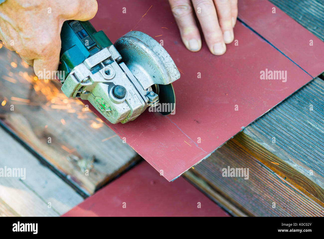 Close-up of worker cutting metal with grinder. Sparks while grinding iron - Stock Image