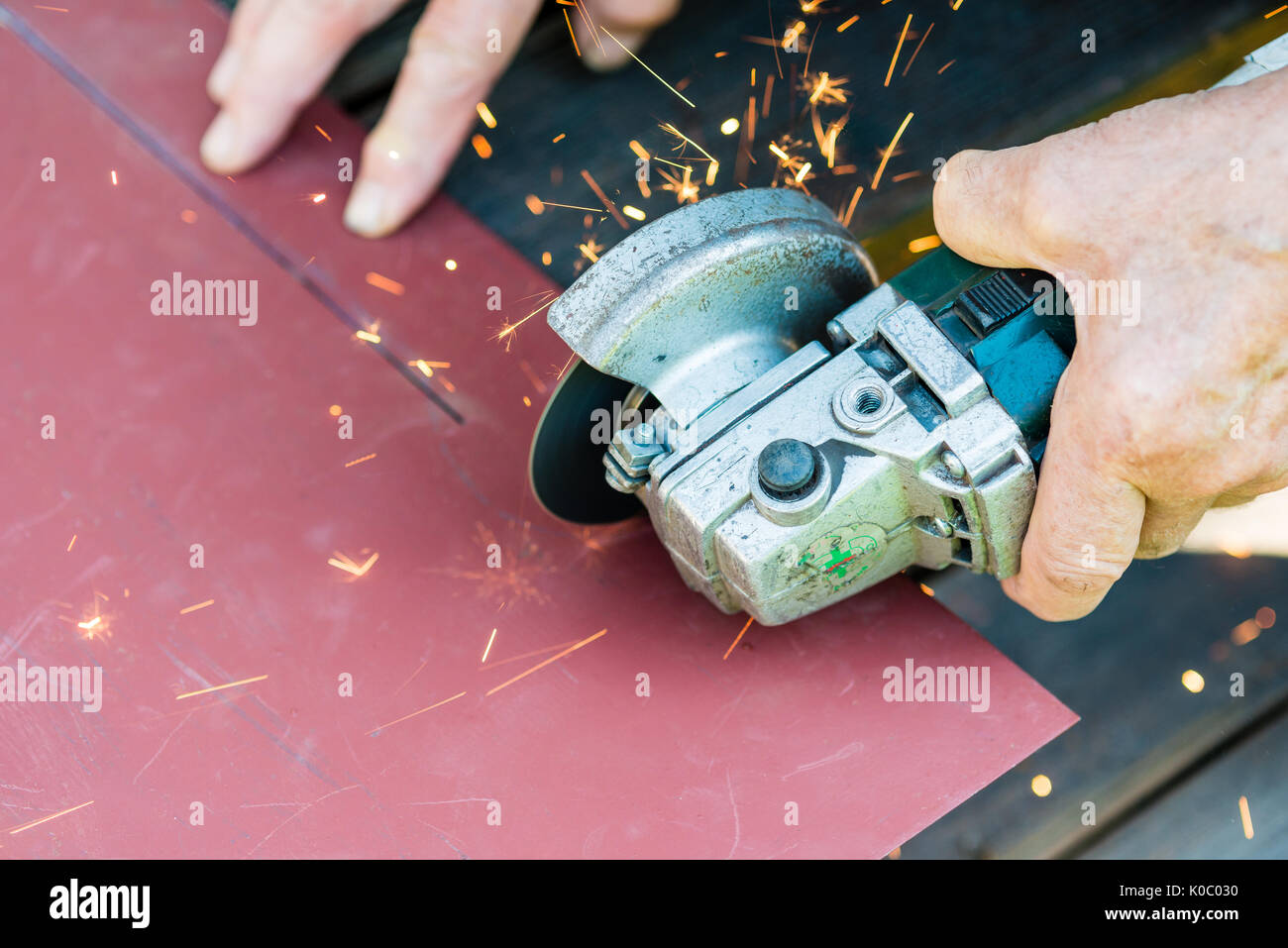 sawing metal with electric grinder - Stock Image
