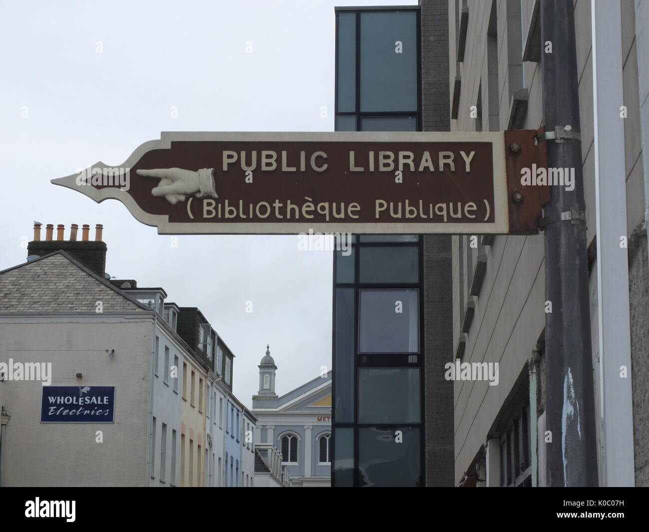 Ornate metal sign for a public library with manicule in dual language of English and Jèrriais (Norman French Language of Jersey), St Helier, Jersey - Stock Image