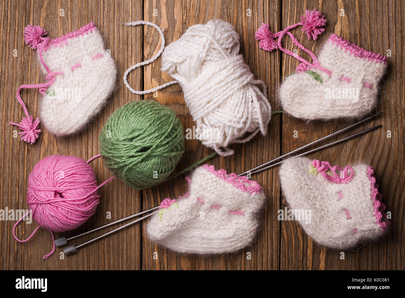 Baby booties with their hands, top view - Stock Image