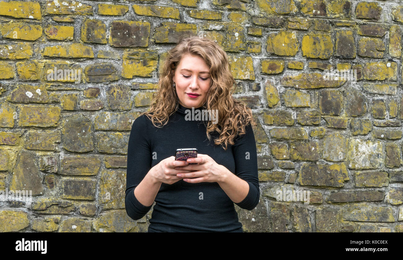 A pretty young woman using her thumbs to enter text and send a message from her mobile phone, while standing in front of a brick wall. - Stock Image
