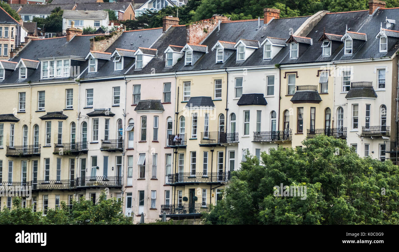 A row of four storey coastal, terraced houses, with a man sitting on his balcony on an overcast day, Ilfracombe town, North Devon, England, UK. - Stock Image