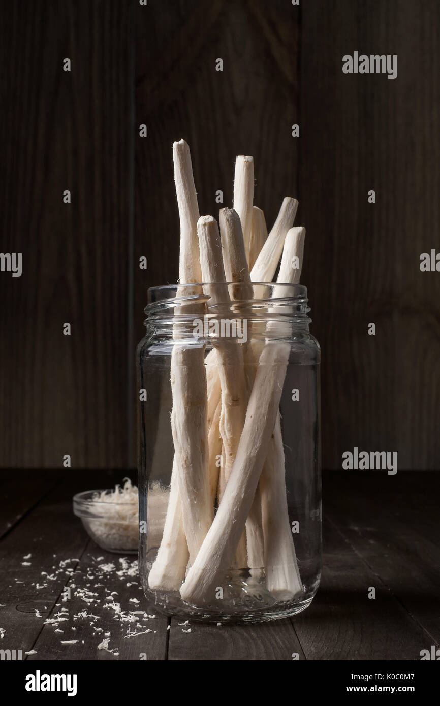 Roots of horseradish in a glass jar, closeup - Stock Image