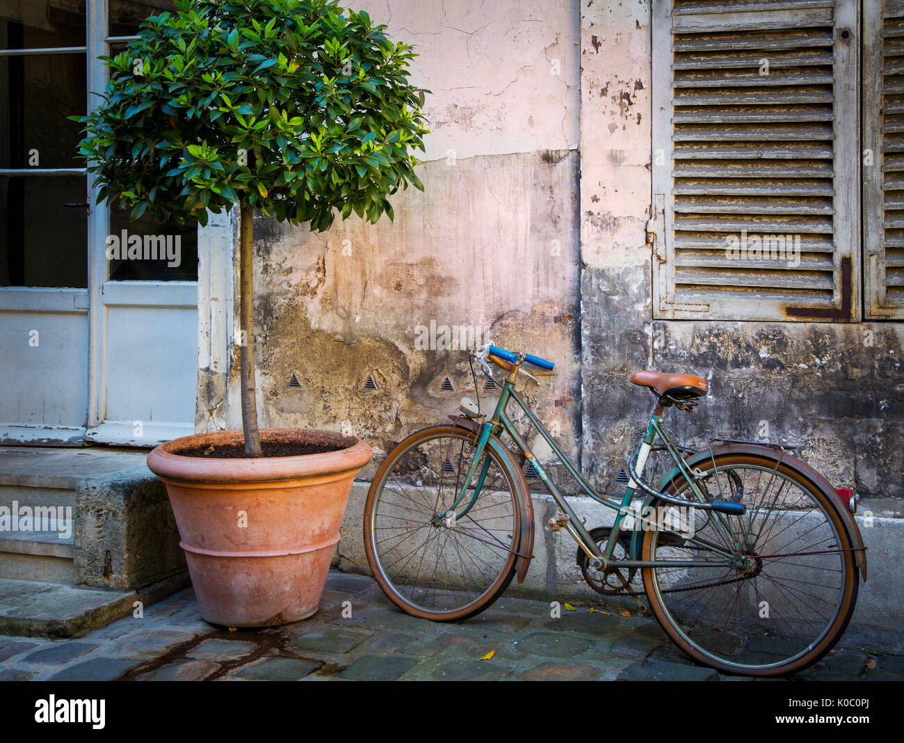 Bicycle parked along ancient wall, Paris, France - Stock Image