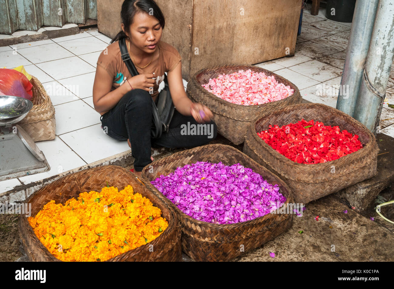 Woman selling flowers for decorating religious offerings, at the market in Ubud, Bali, Indonesia - Stock Image
