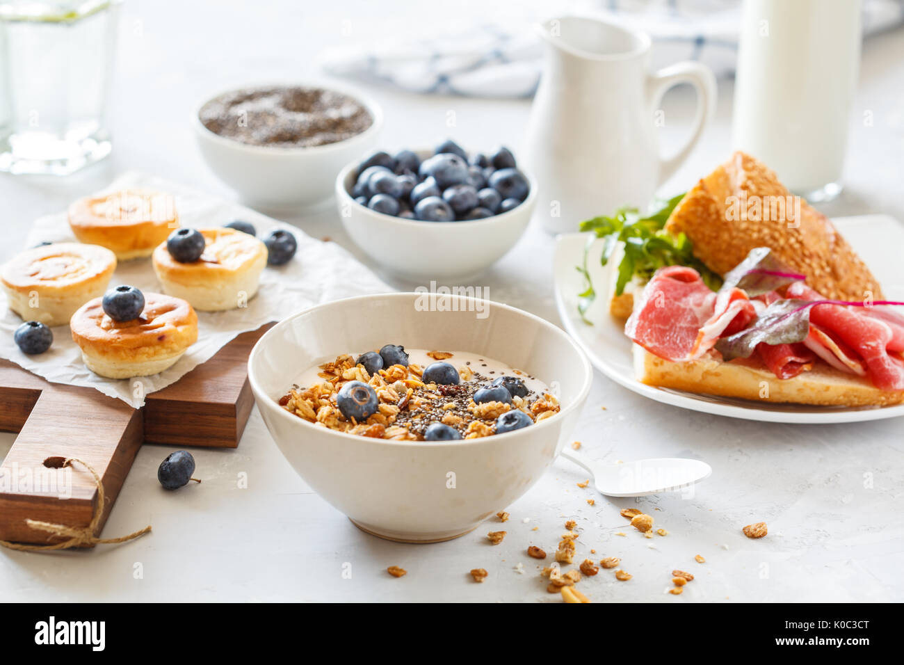 granola with yogurt, sandwiches with meat and avocado, and mini cheesecakes with blueberries for breakfast. - Stock Image