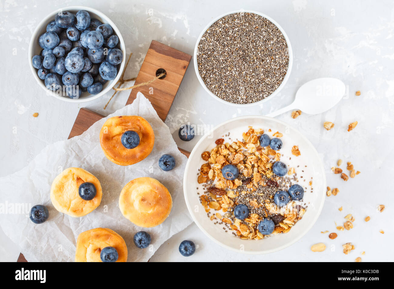 granola with yogurt and mini cheesecakes with blueberries for breakfast. - Stock Image