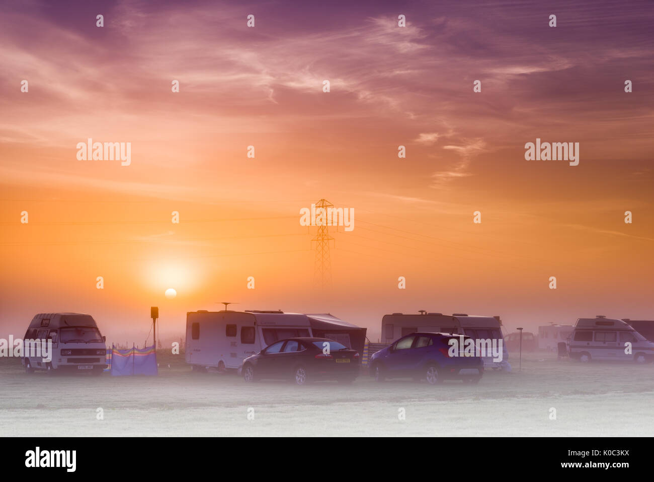 The sun rises over a misty campsite in the UK at dawn on an August morning. - Stock Image