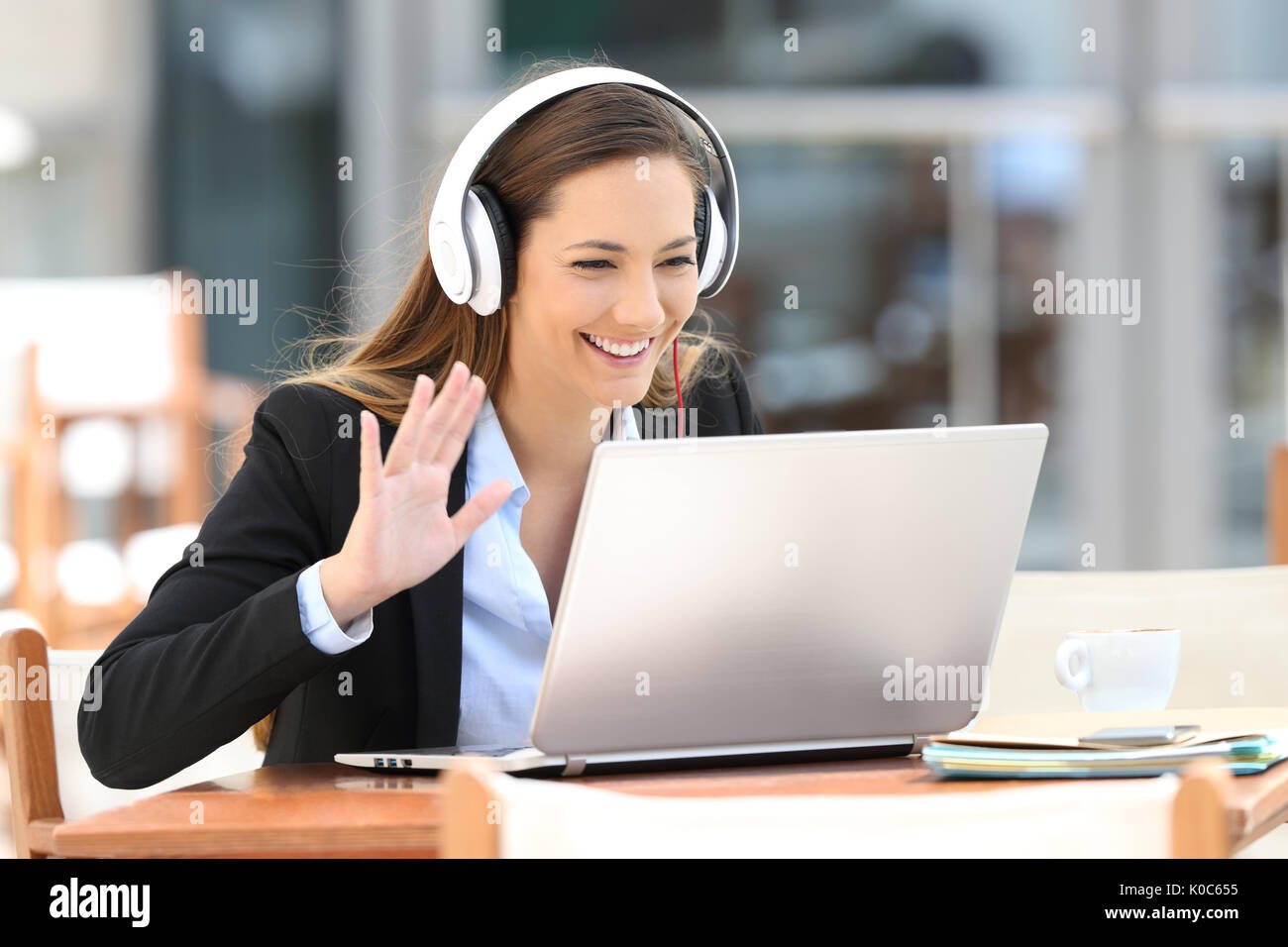 Executive having a video call with a laptop and headphones in a coffee shop - Stock Image
