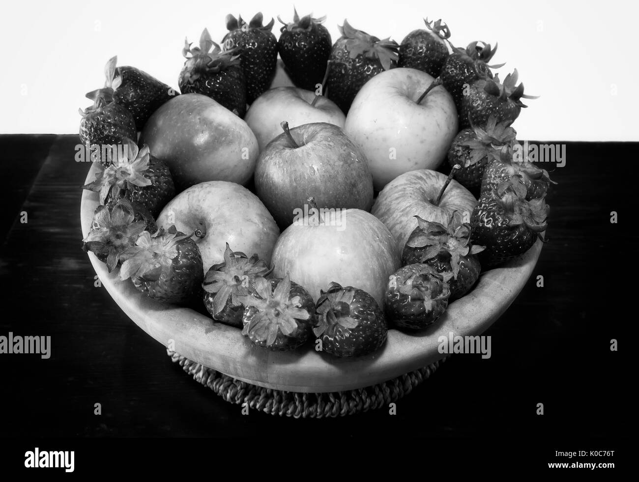 Fruit basket with strawberries and apples inside. Black and white photo - Stock Image