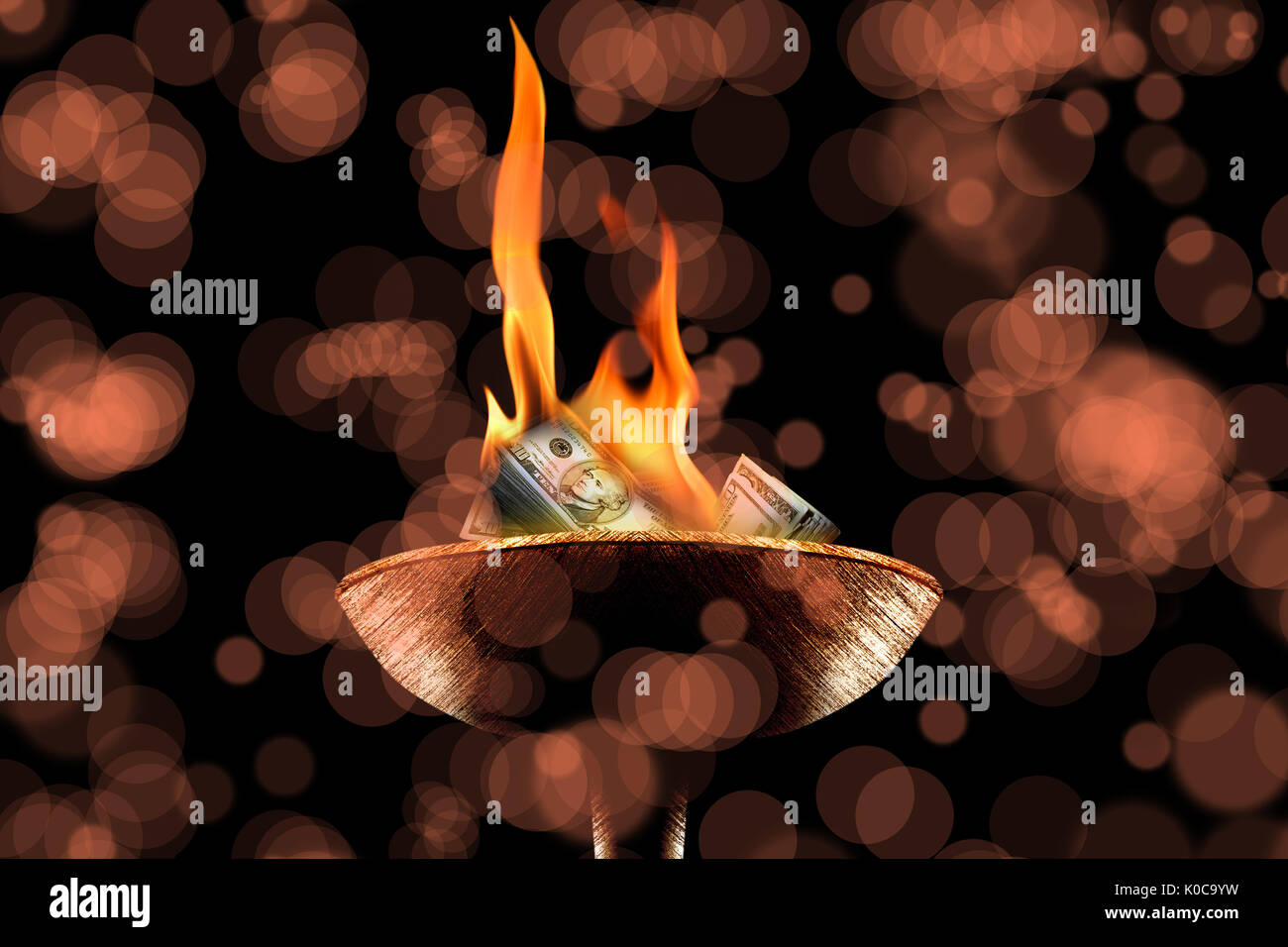 close up shot of money burning in flaming torch. Stock Photo